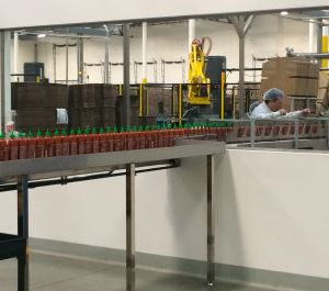 Filled bottle of Sriracha make their way to be boxed up for shipping (photo by Nikki Kreuzer)