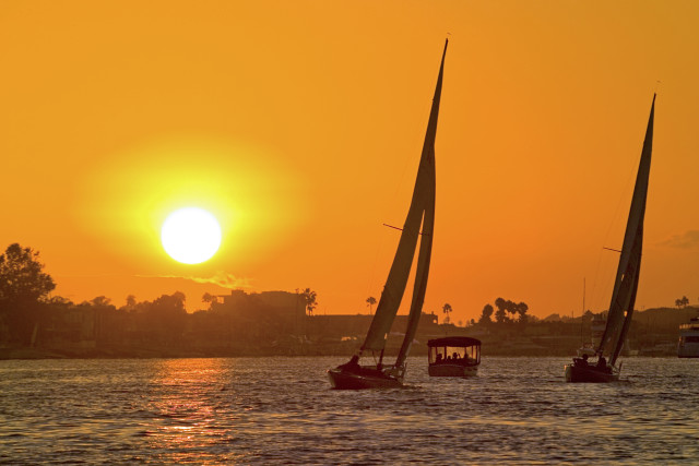 The sun sets on boaters in Newport Harbor at Newport Beach. Photo courtesy of VisitNewportBeach.