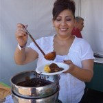 Alma from El Cholo putting mole on a green corn tamal at Pier del Sol