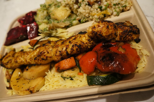 A Yalla plate with chicken skewers, half rice, half squash