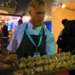 Serving Chef Brian Malarkey's shrimp and clam ceviche with pineapple to people waiting in line
